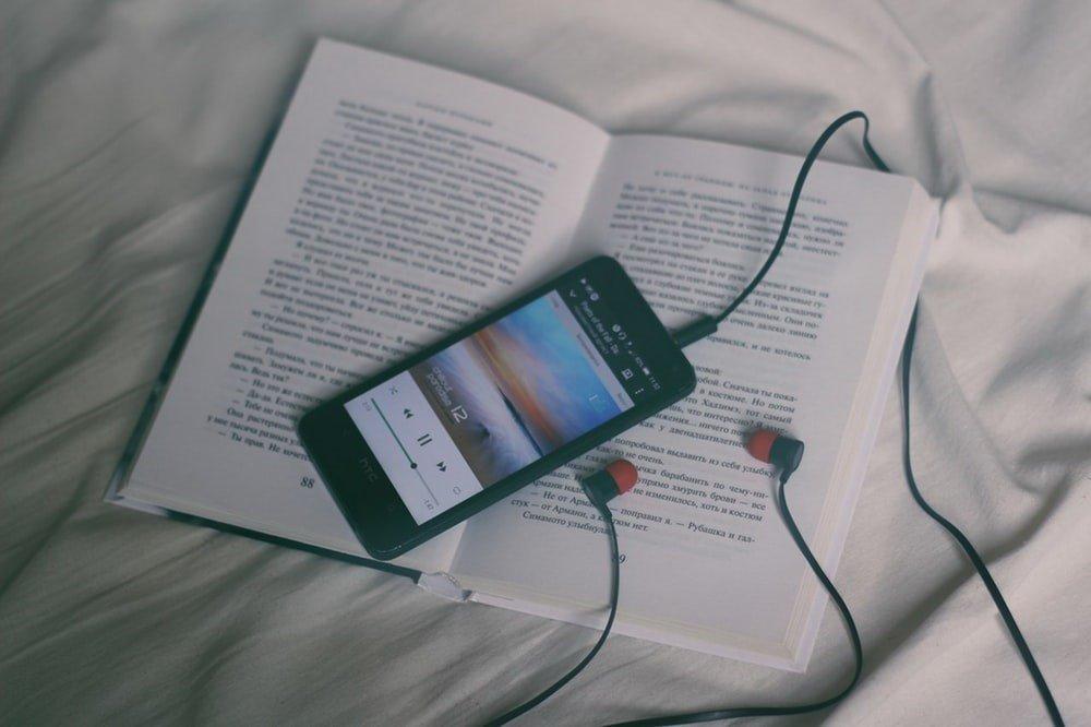 Celular con adifonos encima de un libro.